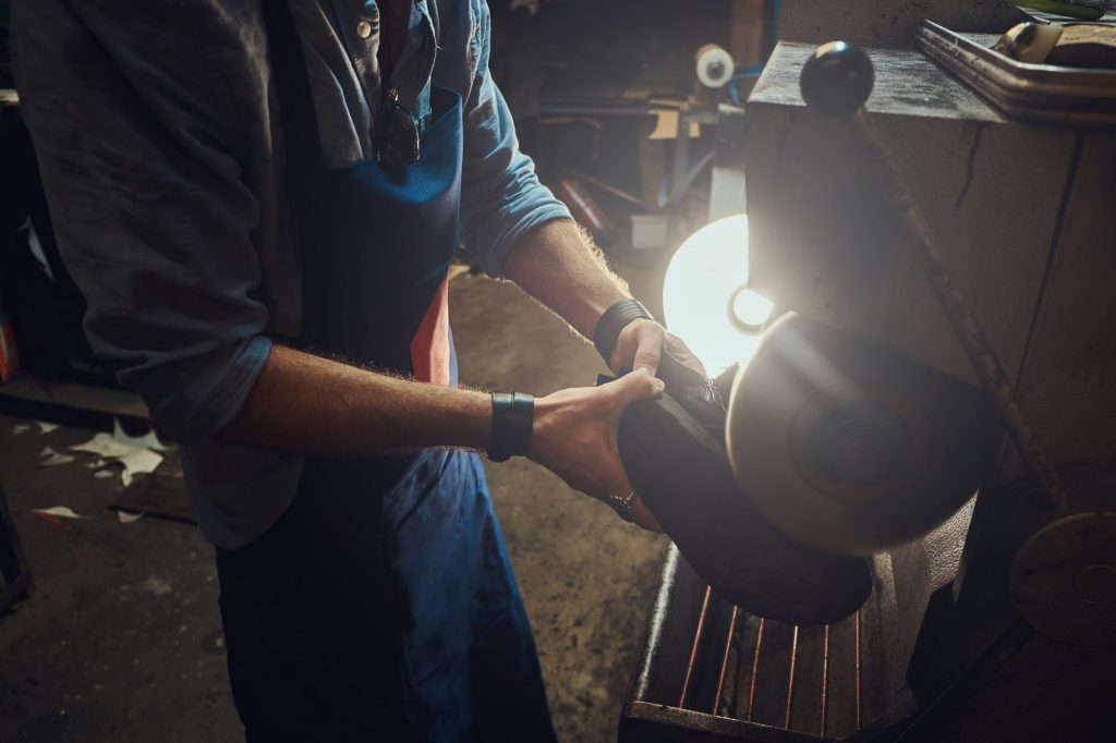 Hands of cobbler, working with mashine tool